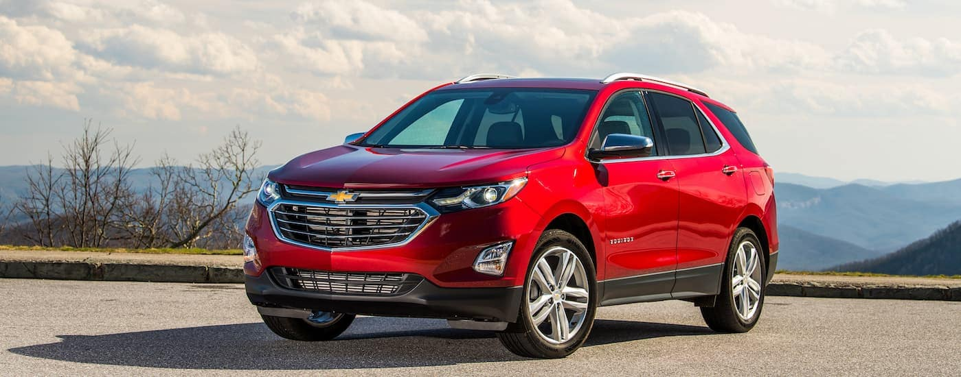 A red 2020 Chevy Equinox, which is an SUV that you'll find at a Chevy dealer near me, is parked in a dirt parking lot.