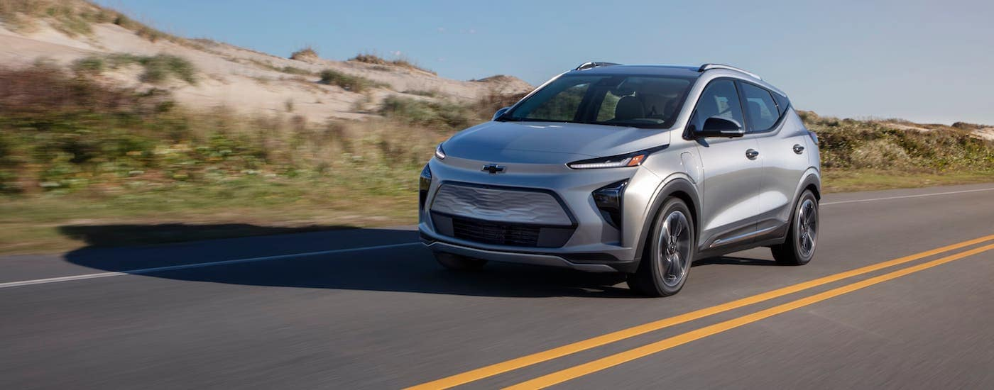 A silver 2022 Chevy Bolt EUV is driving in front of a sand dune after leaving a Chevy dealer near you.