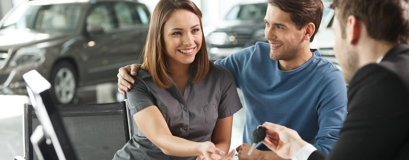 A finance manager is handing a smiling couple their new car keys.