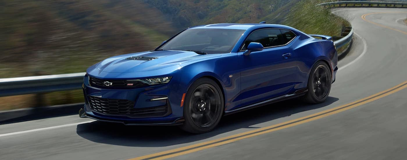 A blue 2020 Chevy Camaro SS is driving on a windy road near Atlanta, GA.