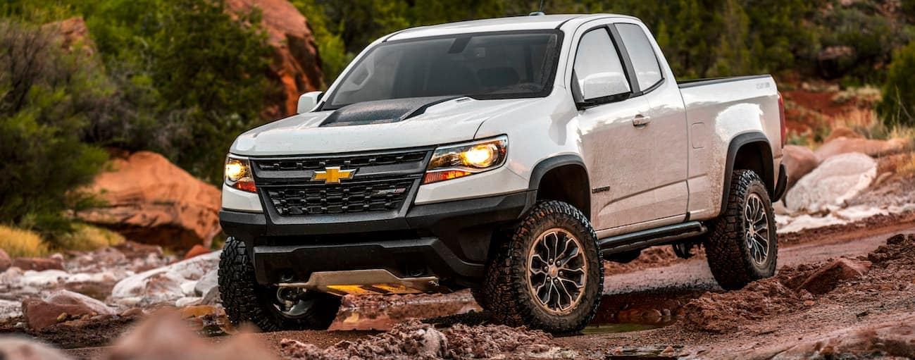 A white 2020 Chevy Colorado is rock crawling.