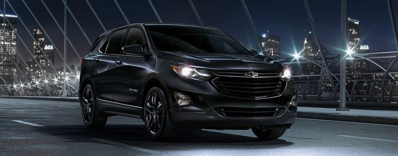 A black 2020 Chevy Equinox is driving on a lit up bridge at night with a city skyline in the background.
