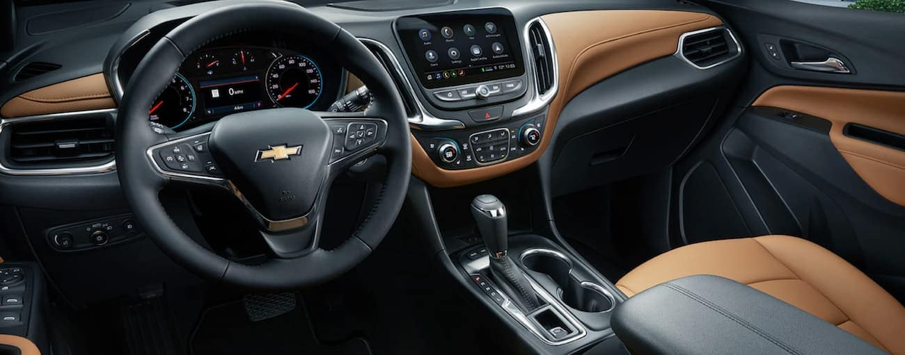 A close up of the black and brown interior that can be found inside a 2020 Chevy Equinox is shown with an infotainment system.