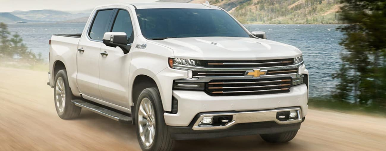 A white 2020 Chevy Silverado 1500 is driving on a dirt road next to a lake.