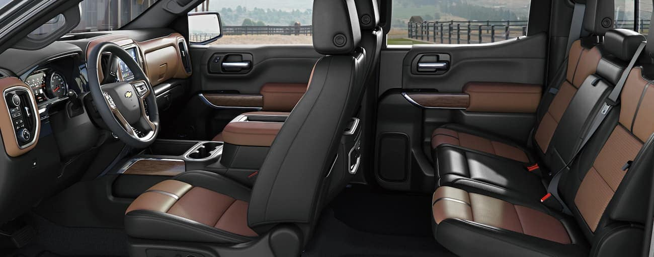A side view of the front and rear brown and black leather seats of a 2020 Chevy Silverado 1500 is shown.