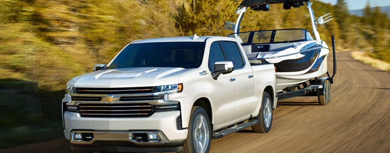 A white 2020 Chevy Silverado 1500 is towing a large boat on a dirt road outside of Buford, GA.