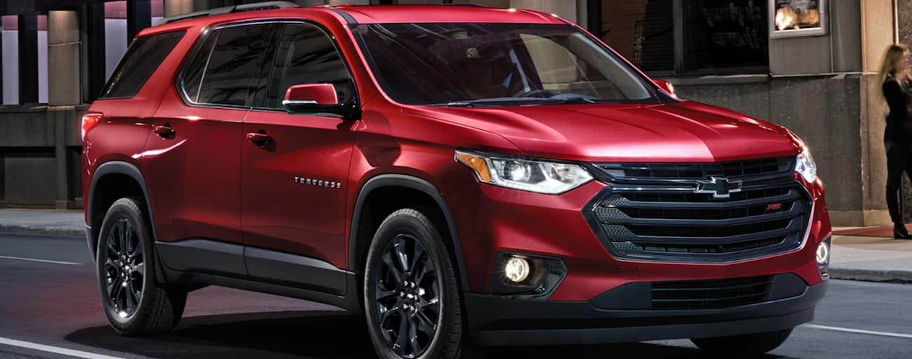 A red 2020 Chevy Traverse is stopped at a red light on a dark lit city street near Buford, GA.