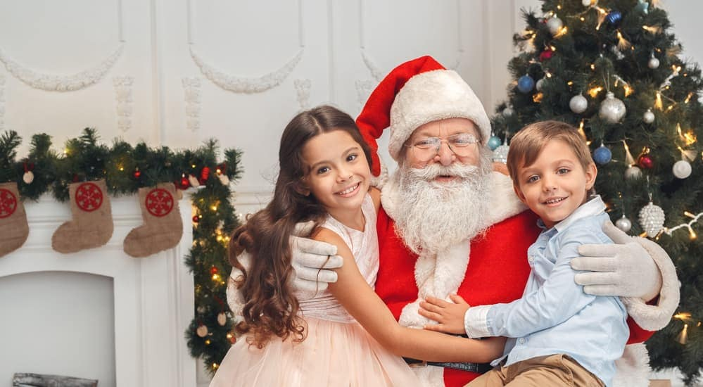 Two smiling kids are sitting on Santa Claus's lap in front of a Christmas tree.