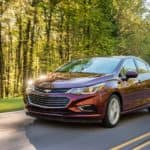 A red 2016 used Chevy Cruze, which is a popular used Chevrolet model, is driving on a treelined road near Buford, GA.