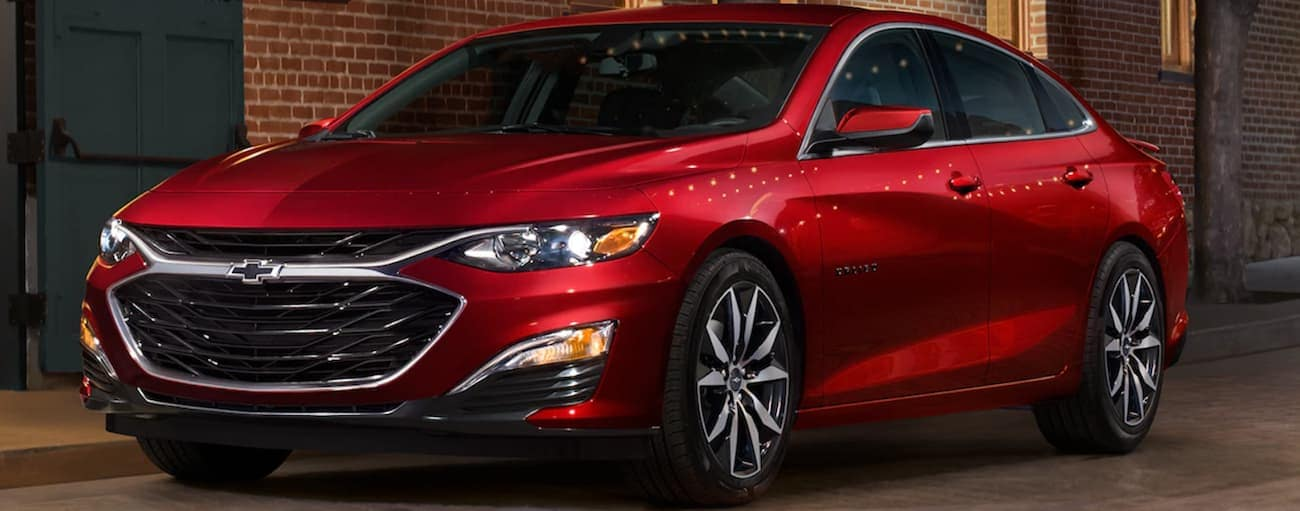 A red 2020 Chevy Malibu is parked under a street light in front of a brick building.