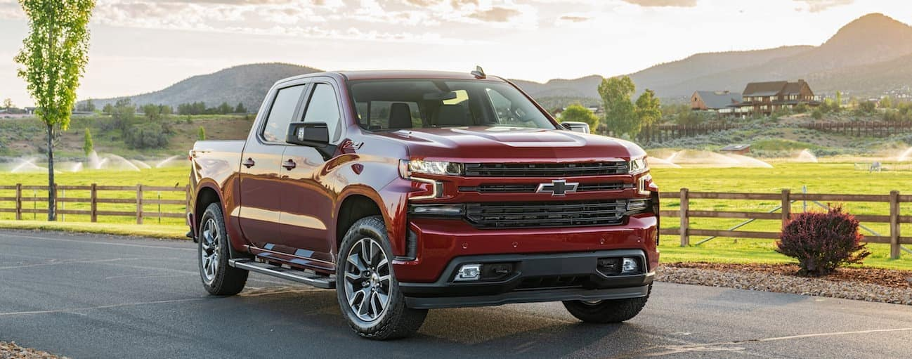 A red 2020 Chevy Silverado 1500, which wins when comparing the 2020 Chevy Silverado 1500 vs 2020 Ram 1500, is parked in front of a farm near Buford, GA.