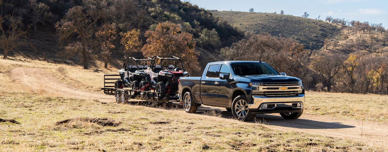 A blue 2020 Chevy Silverado 1500 is towing two side by sides on a dirt road.