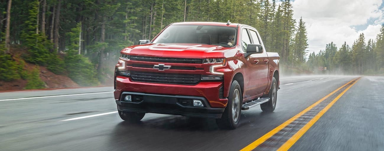 A red 2020 Chevy Silverado is driving on a wet treelined road near Buford, GA.