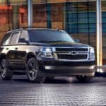 A black 2017 Chevy Tahoe, which is a popular among used SUVs for sale, is parked in front of a glass office building near Buford, GA.