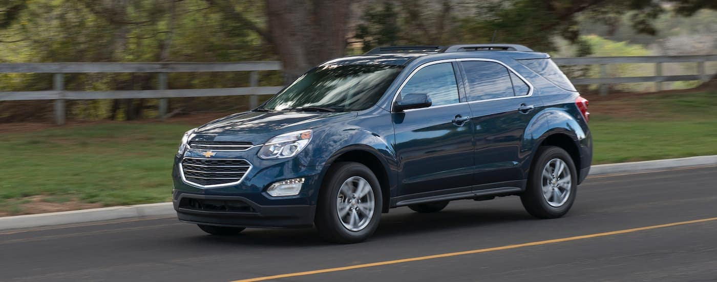 A blue 2016 Chevy Equinox is driving past a fence near Buford, GA.