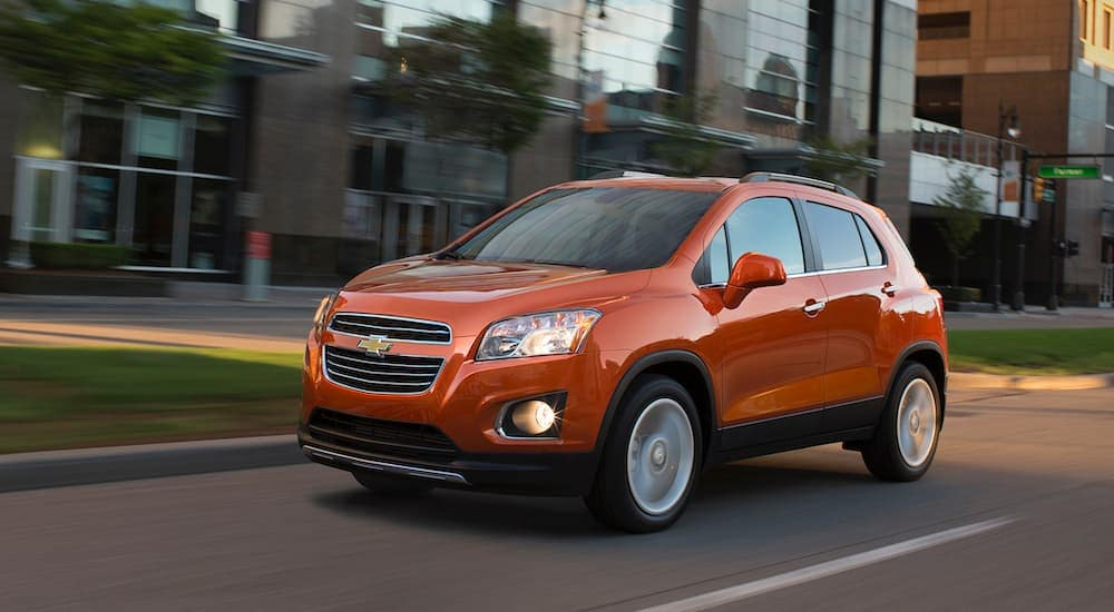 An orange 2016 Chevy Trax, popular among used SUVs for sale, is driving on a city street.