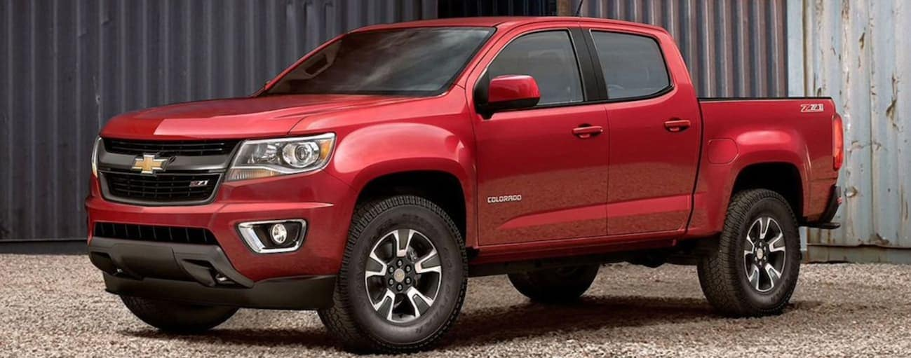 A red 2020 Chevy Colorado is parked on gravel next to metal shipping containers near Buford, GA.