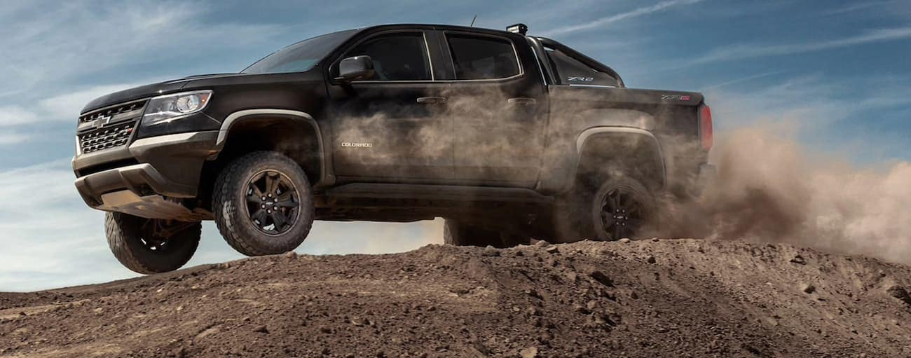 A black 2020 Chevy Colorado ZR2, which wins when comparing the 2020 Chevy Colorado vs 2020 Toyota Tacoma, is driving over a dirt hill near  Buford, GA