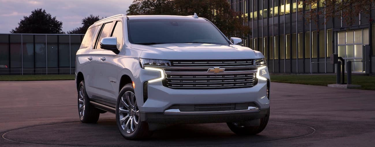A white 2021 Chevy Suburban is parked in front of a large glass windowed building at dusk.