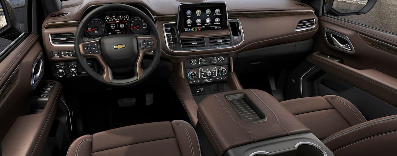 The front brown leather interior of the 2021 Chevy Suburban is shown.