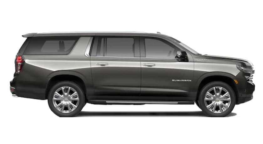 A side view of a grey 2021 Chevy Suburban is facing right.