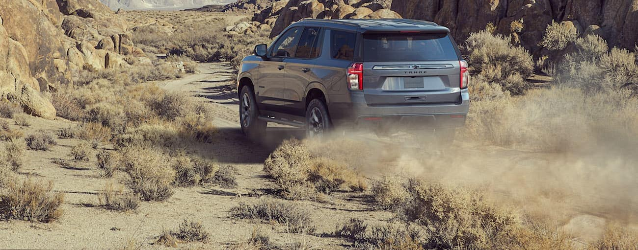 A grey 2021 Chevy Tahoe is driving on a dirt hill with rock hills in the distance.