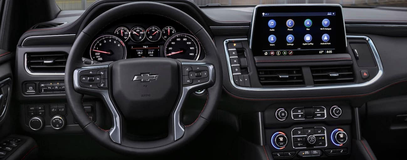 A driver's view of the front black leather interior of a 2021 Chevy Tahoe is shown.