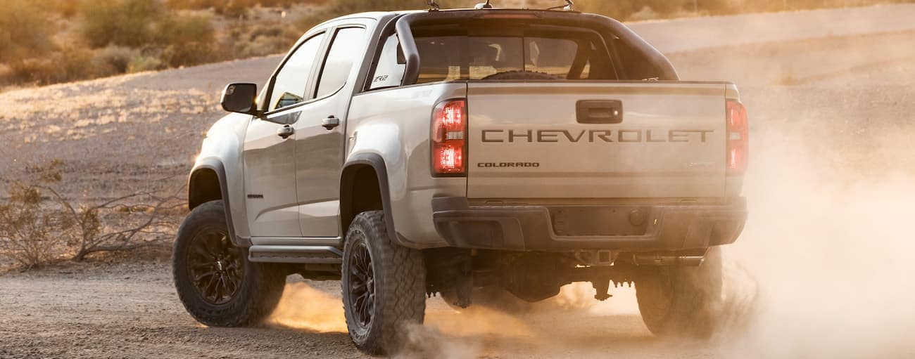 A tan 2021 Chevy Colorado ZR2 is shown from the rear while parked in the dirt.