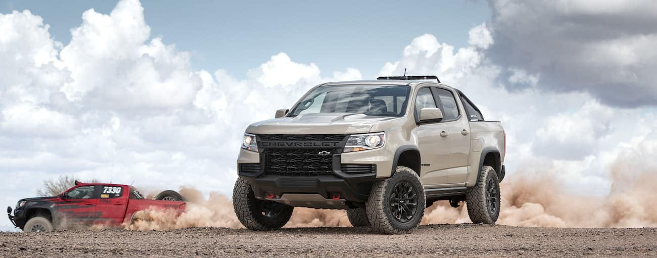 A red 2021 Chevy Colorado Special Edition is racing behind a tan 2021 Chevy Colorado ZR2 in the dirt.