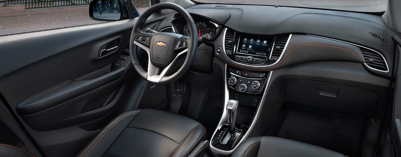The black interior with orange stitching is shown in a 2020 Chevy Trax, the winner of the 2020 Chevy Trax vs 2020 Nissan Kicks comparison.