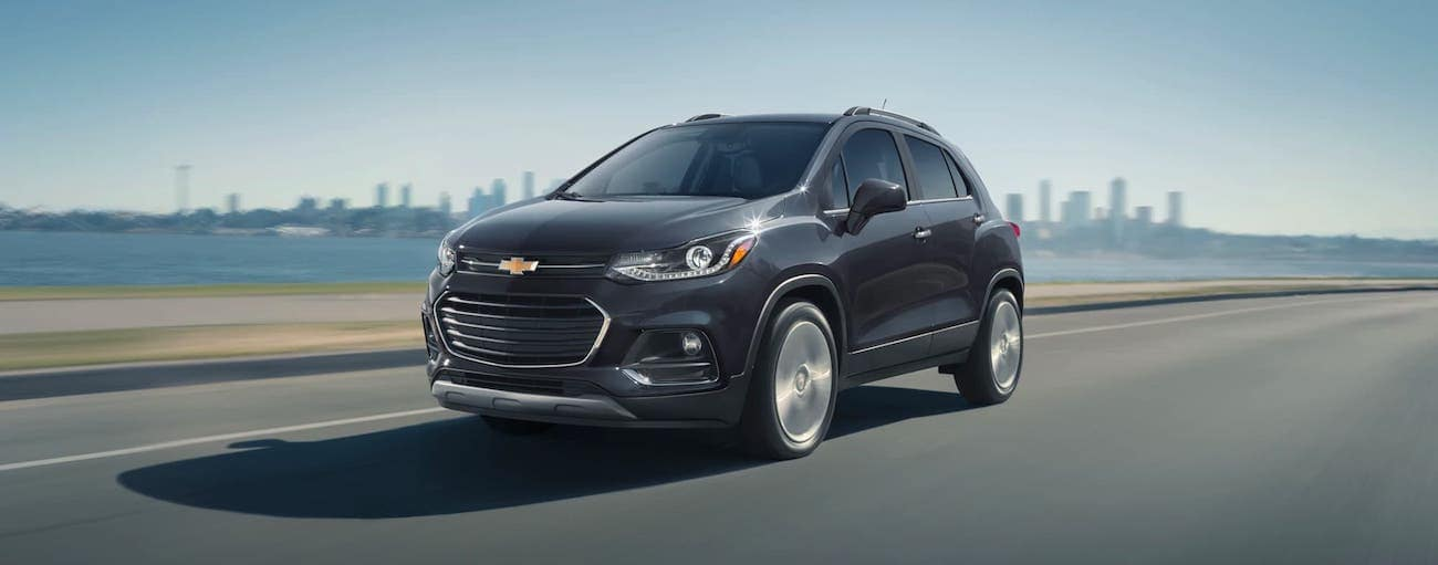 A dark gray 2020 Chevy Trax is driving away from a city skyline.