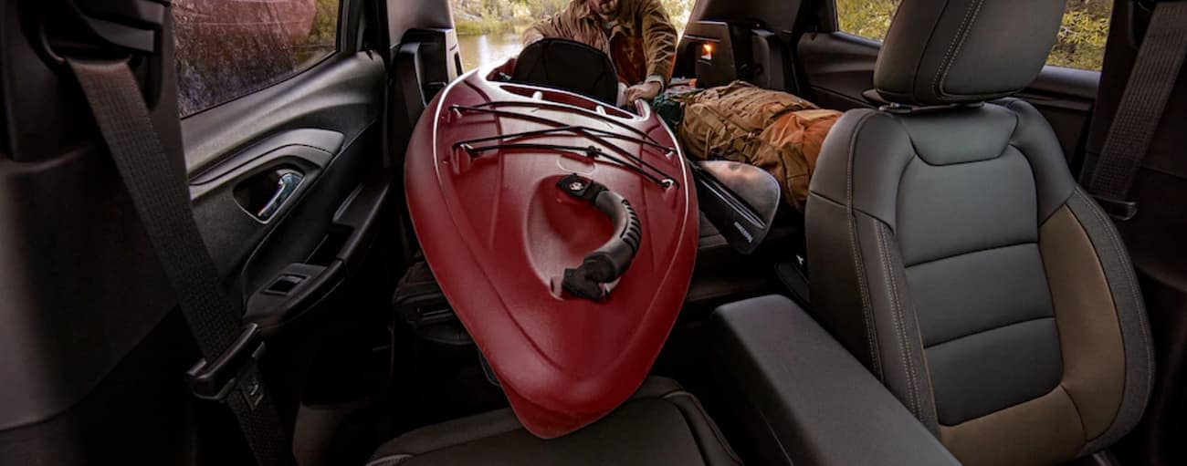 A front to back view of a man sliding a kayak into a 2021 Chevy Trailblazer is shown.