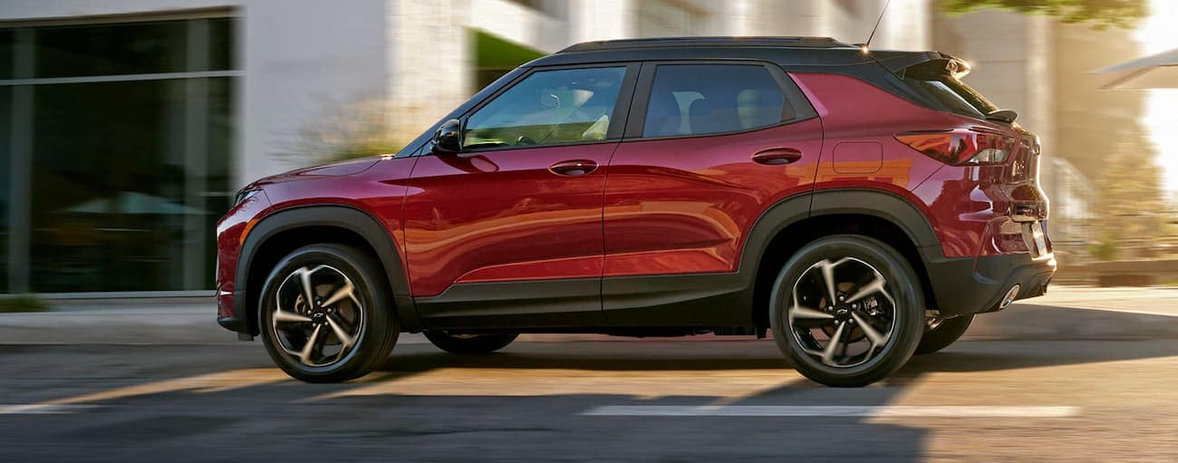 A red 2021 Chevy Trailblazer is driving on a Buford, GA, street after winning the 2021 Chevy Trailblazer vs 2020 Mazda CX-30 comparison.