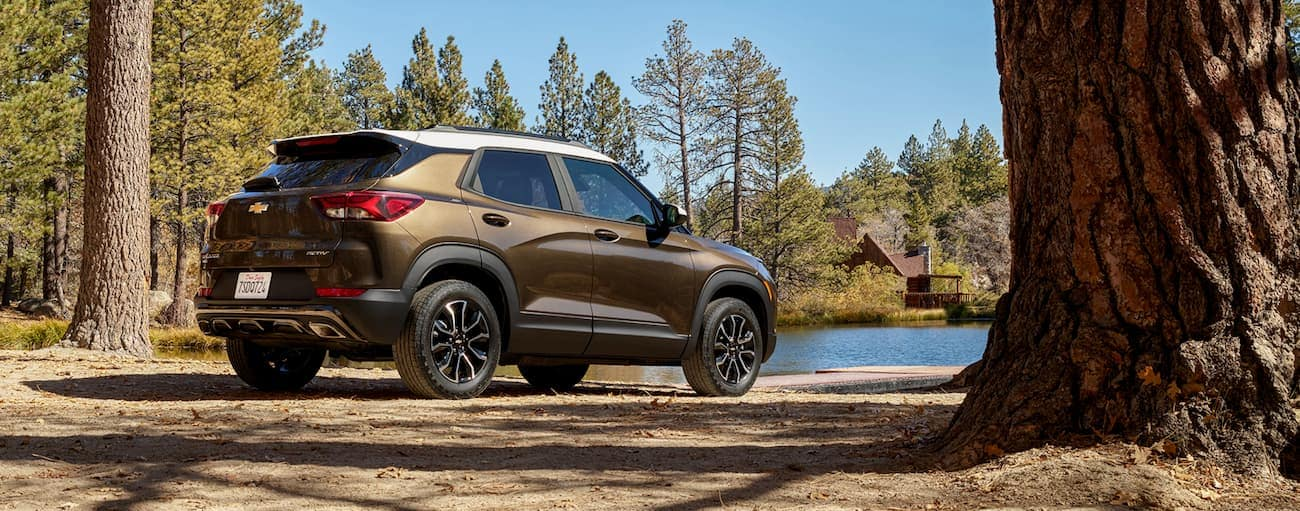 A brown and white 2020 Chevy Trailblazer, which wins when comparing the 2021 Chevy Trailblazer vs 2020 Nissan Kicks, is parked at a lake in the woods.