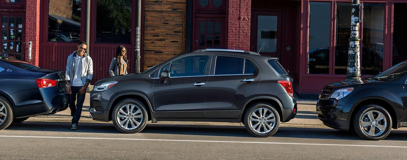 A couple is walking toward a dark grey 2020 Chevy Trax that is parallel parked on a Buford, GA, street.