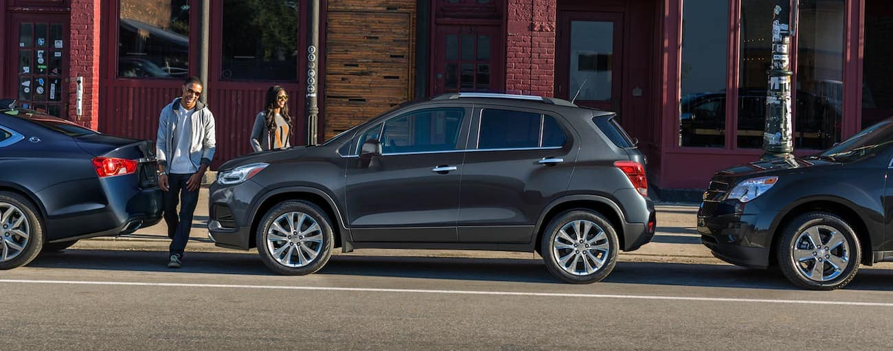 A couple is walking toward a grey 2020 Chevy Trax parked on a Buford, GA street.