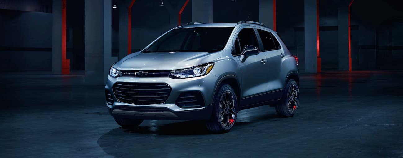 A silver 2020 Chevy Trax is in a dark showroom after winning the 2020 Chevy Trax vs 2020 Honda HR-V comparison.