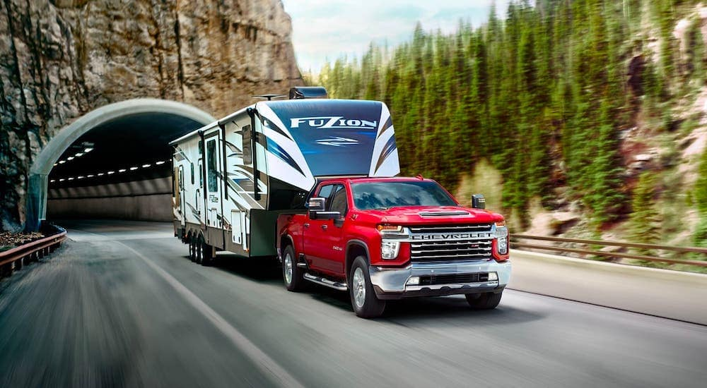 A red 2020 Chevy Silverado 2500HD Z71 is towing a large camper out of a tunnel.
