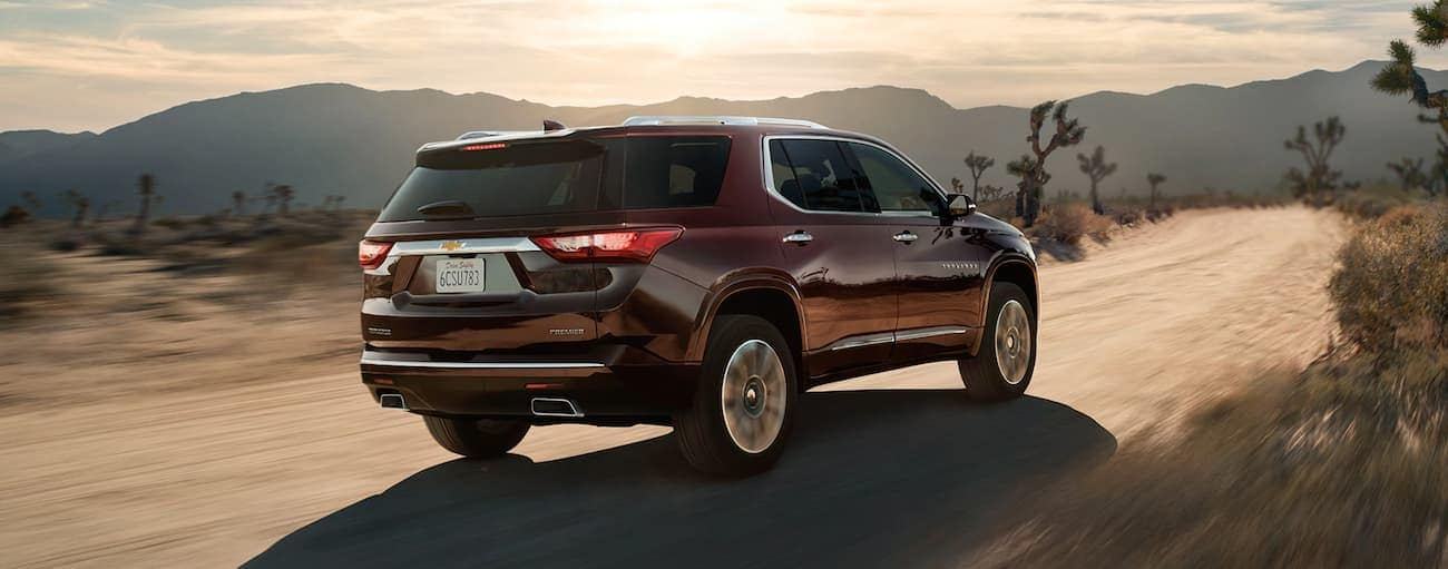 A burgundy 2020 Chevy Traverse is driving toward desert mountains after winning the 2020 Chevy Traverse vs 2020 Ford Explorer comparison.