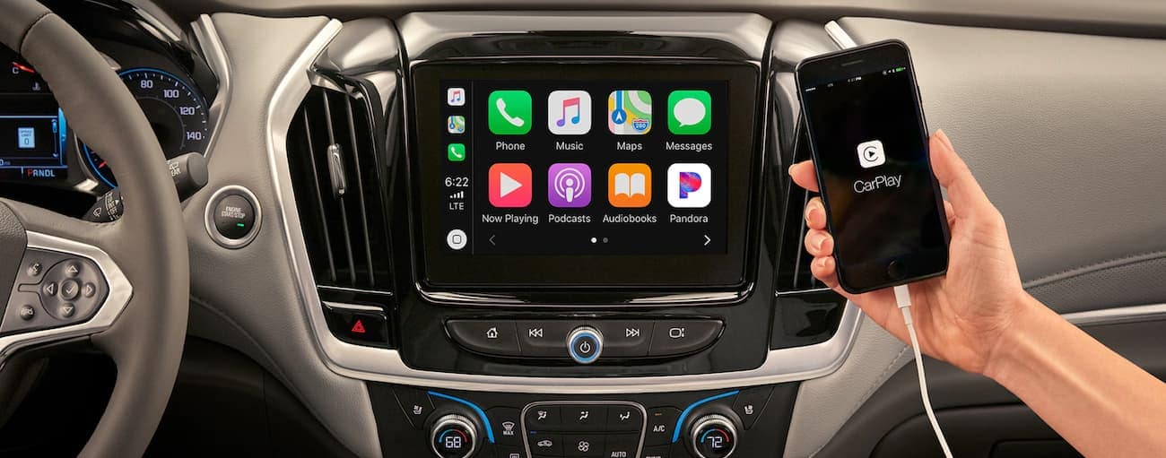 The Apple Car Play app is shown on a smart phone in front of the 2020 Chevy Traverse's infotainment screen.