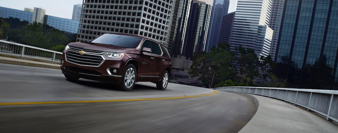 A burgundy 2020 Chevy Traverse is driving away from a city after winning the 2020 Chevy Traverse vs 2020 Honda Pilot comparison.
