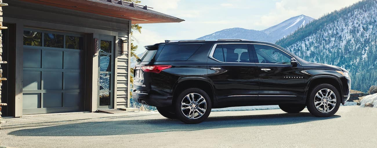 A black 2020 Chevy Traverse is parked at a cabin with mountain views.