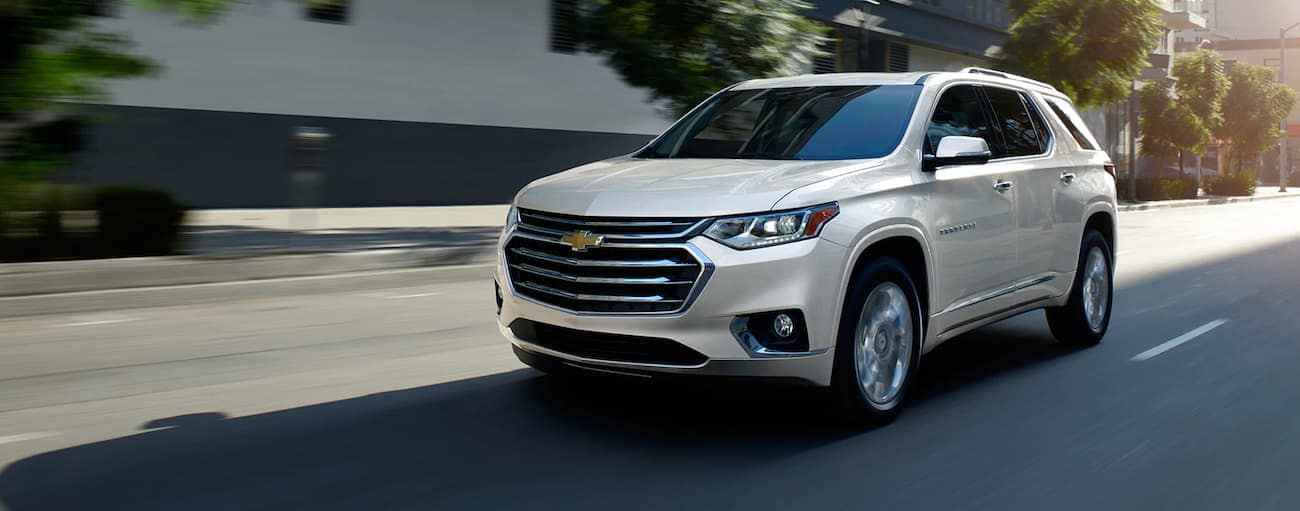 A white 2020 Chevy Traverse is driving on a city street near Buford, GA, after winning the 2020 Chevy Traverse vs 2020 Mazda CX-9 comparison.