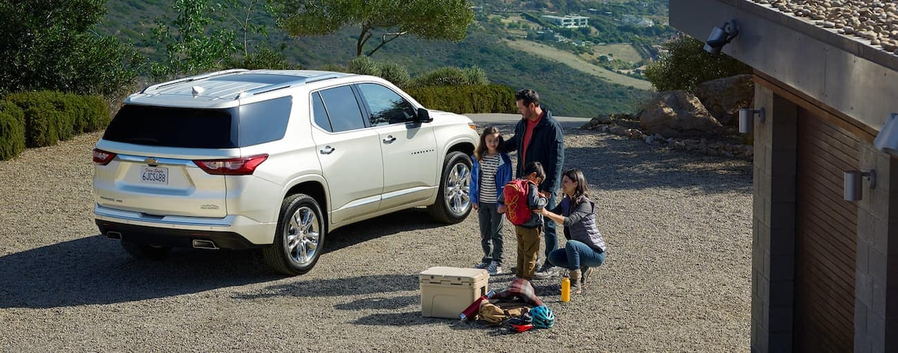 A family at a mountain home is getting ready to load up their white 2020 Chevy Traverse, which wins when comparing the 2020 Chevy Traverse vs 2020 Nissan Pathfinder.