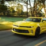 A yellow 2018 Chevy Camaro is driving on a tree-lined road near Buford, GA.