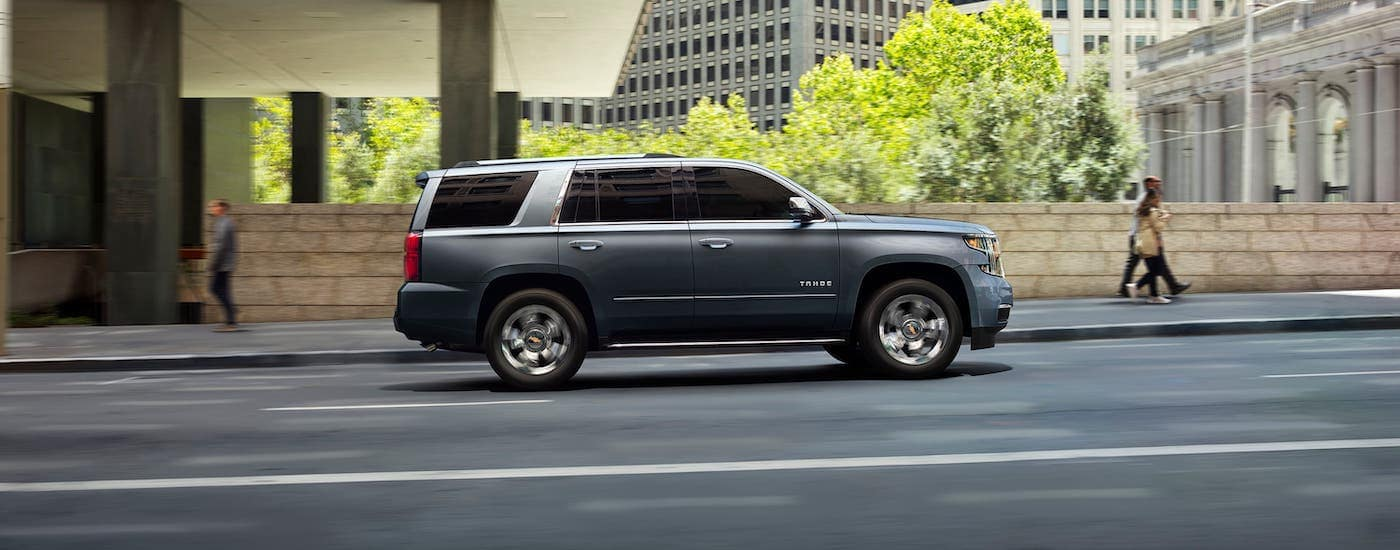 A gray 2020 Chevy Tahoe is shown from the side driving on a city street after winning the 2020 Chevy Tahoe vs 2020 Nissan Armada comparison.