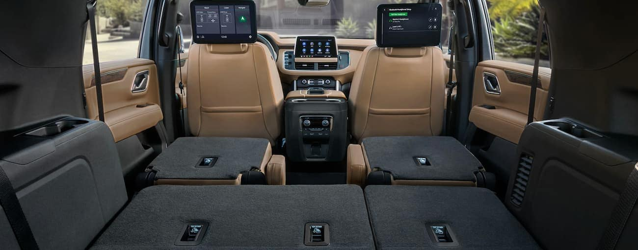 The tan and grey interior is shown in a 2021 Chevy Tahoe with the seats folded down.