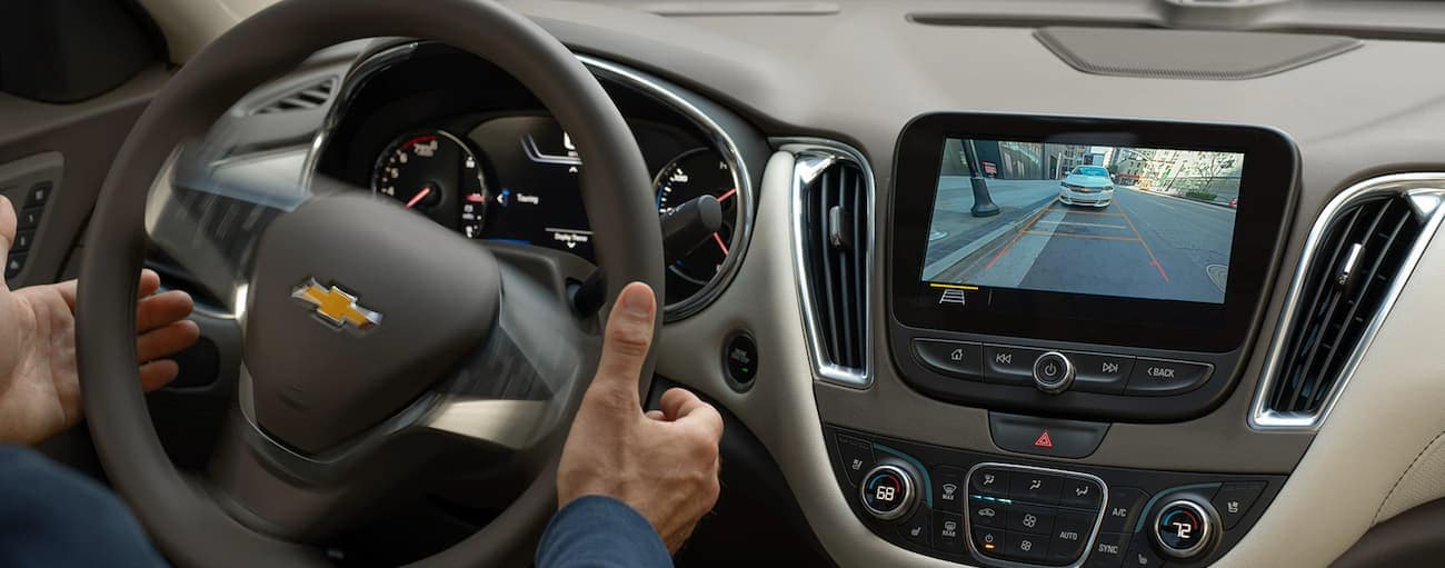 The rear view camera is shown in use in a 2020 Chevy Malibu.