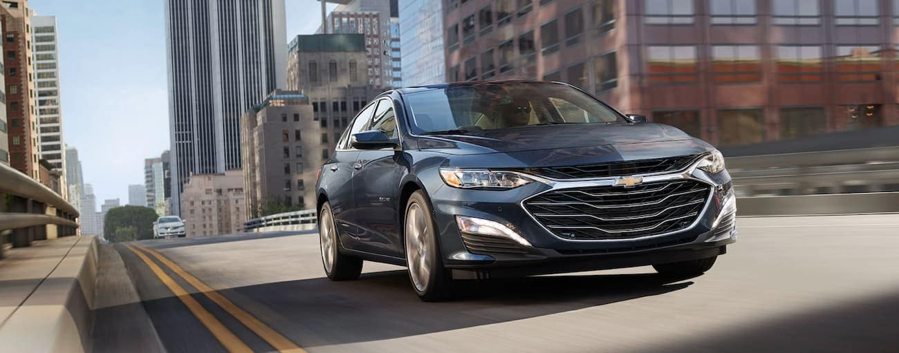 A blue 2020 Chevy Malibu is driving down a city street near Buford, GA, after winning the 2020 Chevy Malibu vs 2020 Nissan Altima comparison.