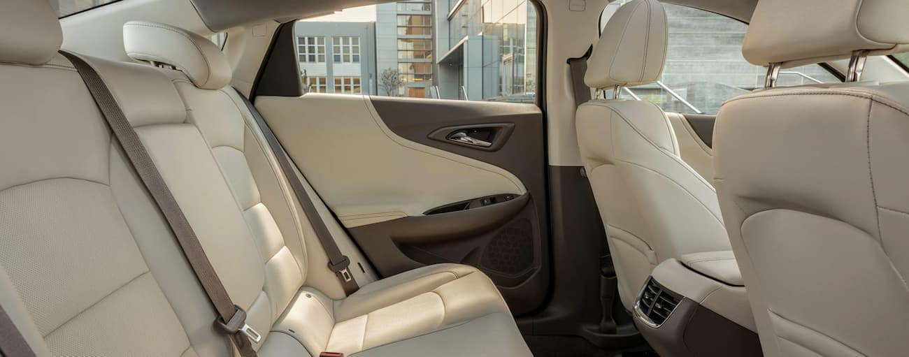 The cream interior with a focus on the rear seats is shown in a 2020 Chevy Malibu.